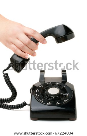 A hand  holding the handset of an old black vintage rotary style telephone isolated over white. - stock photo