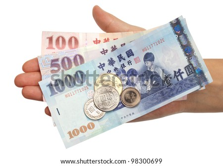 A hand holding the most commonly used coins and notes in Taiwan. - stock photo