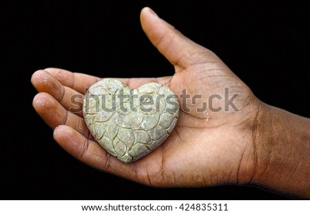 A hand holding up a heart of stone, isolated on black background. - stock photo
