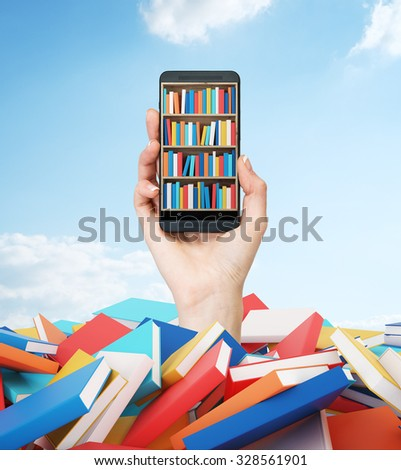 A hand holds a smartphone with a book shelf on the screen. A heap of colourful books. A concept of education and technology.Cloudy blue sky on the background. - stock photo
