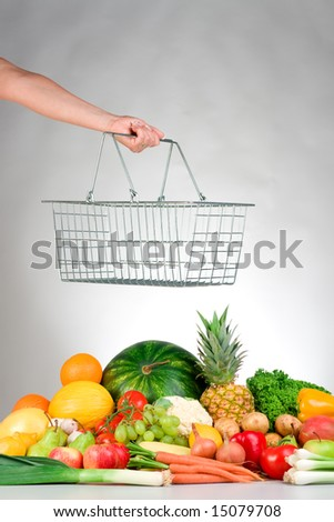 A hand holds a wire shopping basket over a selection of fresh produce. - stock photo