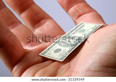 a hand holds miniature money representing the world financial crisis - stock photo