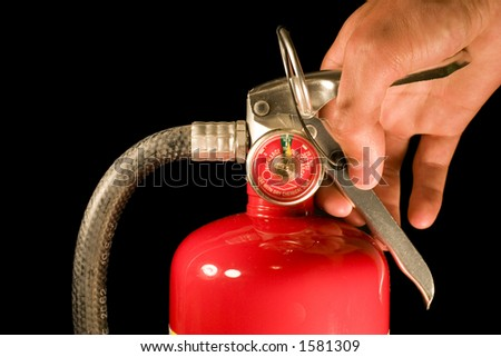 A hand holds the handle of a fire extinguisher - stock photo