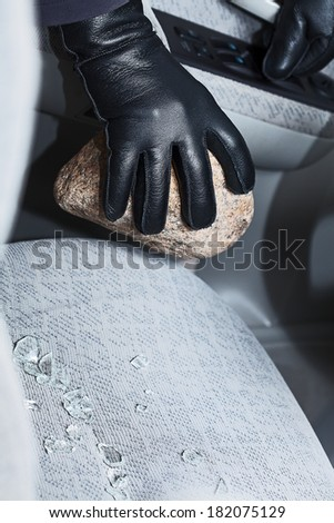 A hand in a glove holding a stone after breaking into a car - stock photo