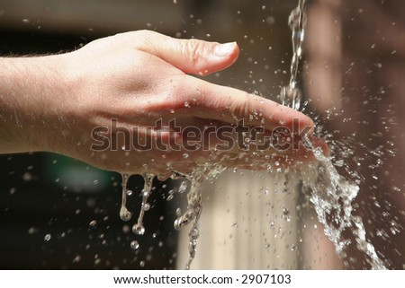A hand in a waterflow