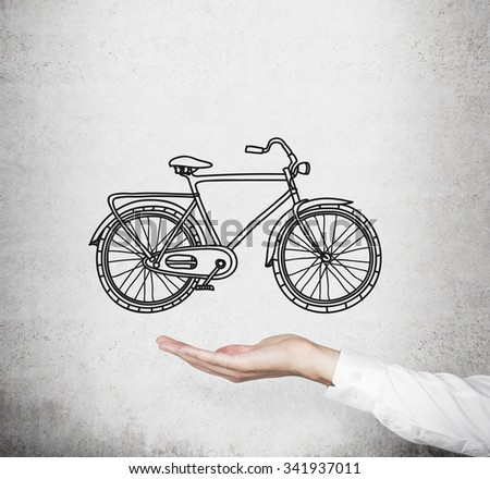 A hand in formal white shirt holds a model of a sketched bicycle. Concrete wall on background. A concept of commuting or travelling. - stock photo