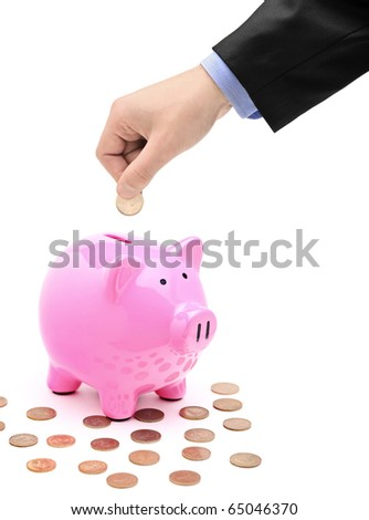 A hand inserting a coin into a pink piggy bank isolated against white background - stock photo