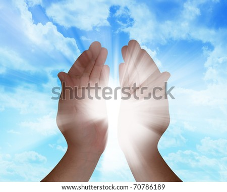 A hand is catching the sun rays in their hands with clouds in the background. - stock photo