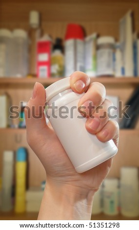 A hand is holding a blank white medical prescription bottle and there is a medicine cabinet in the background with shadow. Photo can be used for addiction, pain or healthcare. - stock photo