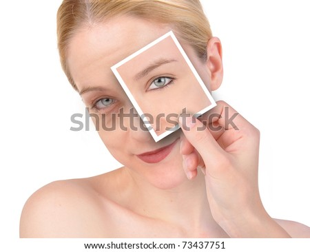 A hand is holding up a photo of a young, eye on a wrinkled woman's face. She is isolated on a white background. - stock photo