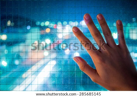 a hand is on the window which is protected by wire net at night - stock photo