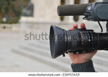 A hand is operating a professional video camera  - stock photo