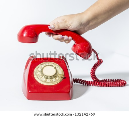 a hand is picking a red phone old