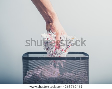 A hand is putting a bunch of shredded paper in a waste paper basket - stock photo