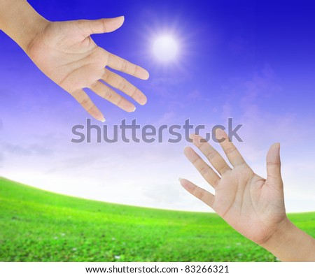 A hand is reaching out in the sky for help - stock photo