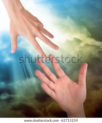 A hand is reaching out or grabbing for help from another hand in the sky. Clouds are in the sky as the background. Use it for a safety, religious or support concept. - stock photo