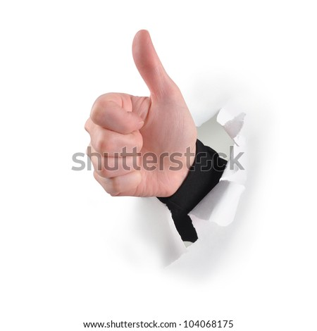 A hand is ripping through white paper and gives a thumbs up for acceptance or success. - stock photo