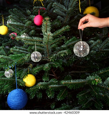 A hand is shown putting a disco ball ornament on a Christmas tree. Square format. - stock photo