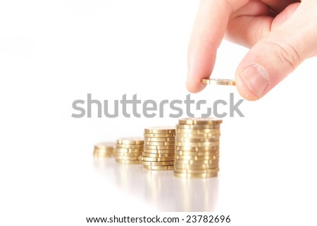 A hand is stacking up coins. The last coin is dropped. The coins are mirrored. Isolated over white. Ideal Businesshot.