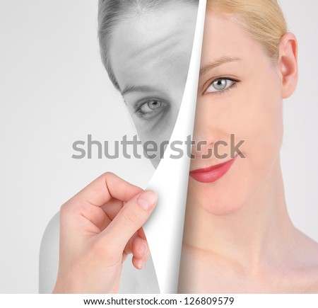 A hand is turning a paper of a young, eye on a wrinkled woman's face in black and white for a youth concept. - stock photo