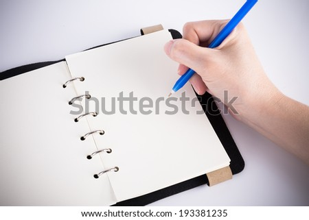A hand is writing on blank page notebook