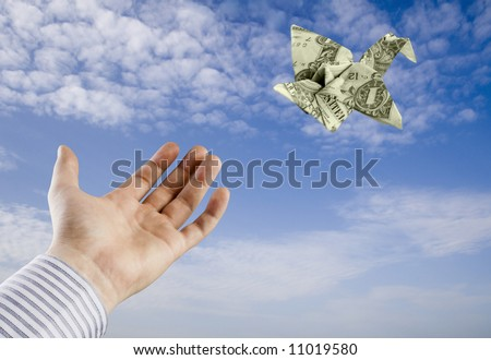 A hand letting go of a 1 dollar origami Bird - stock photo