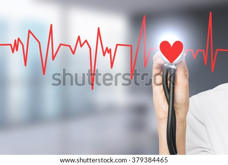 A hand listening to a red heart with a phonendoscope, the heart is a part of a cardiogram. Blurred office background. Concept of medical examination. - stock photo