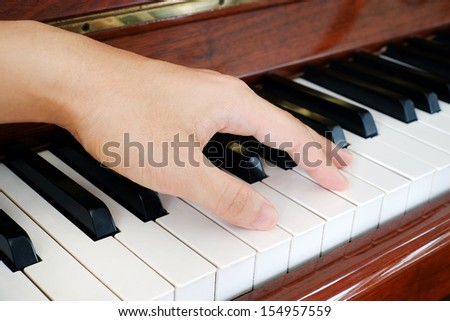 A hand of a performer on the piano - stock photo