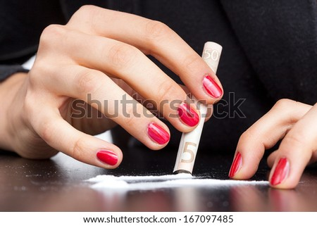 A hand of an addicted woman making a cocaine line using a note - stock photo