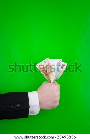 A hand of an executive holding Euro notes, on a green background.
