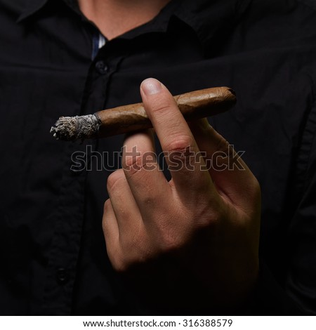 a hand of man holding a cigar