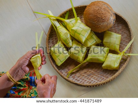 A hand of old woman preparing ketupat or South East Asian rice cakes bundle, often prepared for festivities and celebratory occasions. selective focus