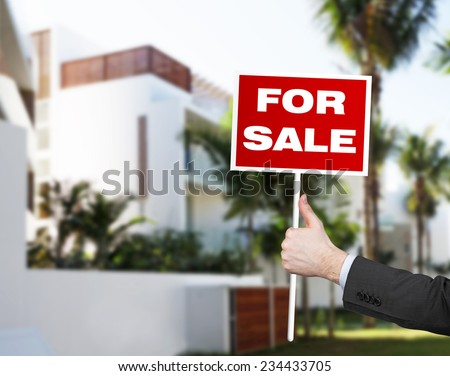 A hand of property agent is holding a Home for Sale table, real estate sign.