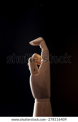 A hand of wood doll make two fingers to two(2) and ear isolated black background with back light in the studio. - stock photo