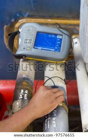 a hand of worker checking quality of weld using industrial ultrasonic device - stock photo