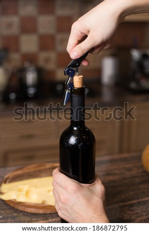 A hand opening a bottle of wine with corkscrew