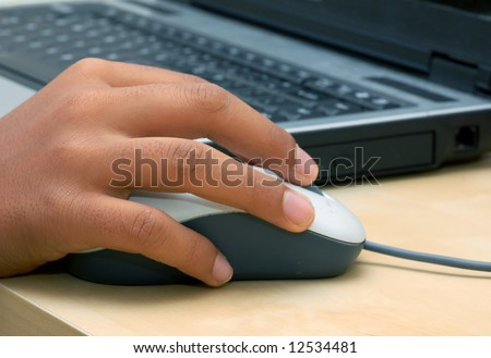 a hand operating a mouse with laptop in the background
