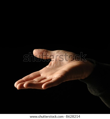 a hand out palm up in plea or want against black - stock photo