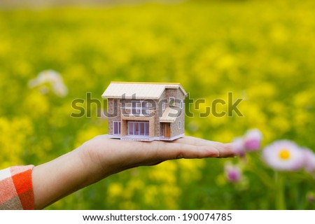 A hand outstretched with a model house on it. - stock photo