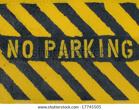 "A hand-painted ""No Parking"" sign on blacktop. - stock photo"