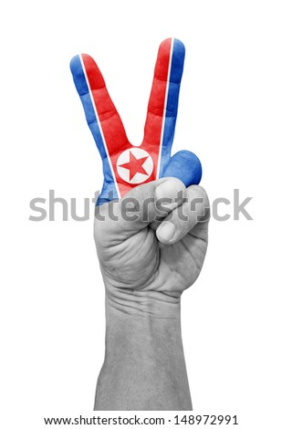 A hand painted with a North Korea flag making a V for victory symbol, isolated against white. - stock photo