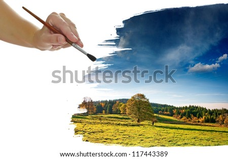 a hand painting a beautiful autumnal landscape - stock photo