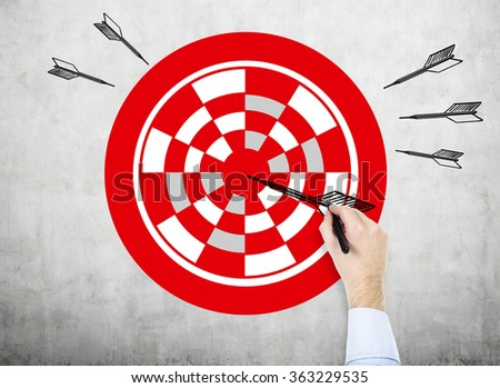 A hand painting a red target with a pen, black painted arrow in the centre, five darts around the target, concrete background. Concept of setting a goal.