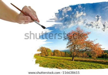 a hand painting an autumnal landscape - stock photo