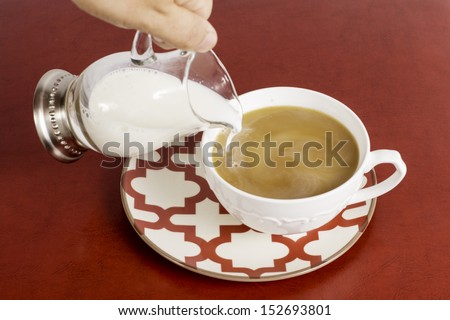 A hand pouring cream into a cup of coffee. - stock photo