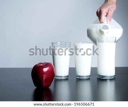 A hand pouring the third of three glasses of milk and a shiny, red apple. - stock photo