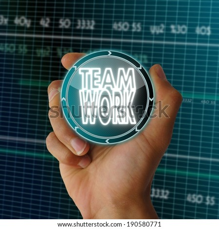 a hand presents interface round button with a Teamwork icon on it in front of a electronic data table from stock market