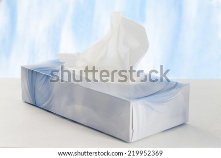 A hand pulls a tissue from a tissue box. - stock photo