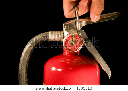 A hand pulls the pin on a red fire extinguisher - stock photo