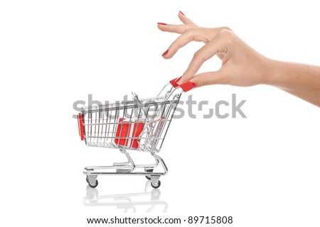 A hand pushing a red shopping cart isolated on a white background. - stock photo